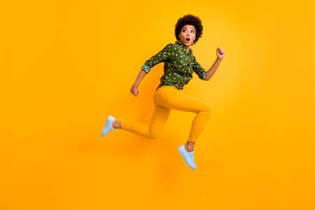 Full body photo of crazy dark skin curly lady jumping up high rushing fast home see street dangerous maniac wear green dotted shirt pants sneakers isolated yellow color background