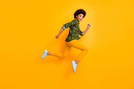 Full size photo of crazy dark skin curly lady jumping up high rushing fast discount shopping black friday low prices wear green dotted shirt pants shoes isolated yellow color background Zdjęcie Seryjne