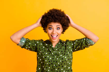 Portrait of funny funky afro american girl hear wonderful bargain novelty impressed scream wow ogm touch hands hair wear stylish clothes isolated over bright color background Banque d'images