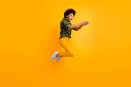 Full body photo of crazy dark skin curly lady jumping high making swimming moves excited to start competition wear green dotted shirt trousers isolated yellow color background