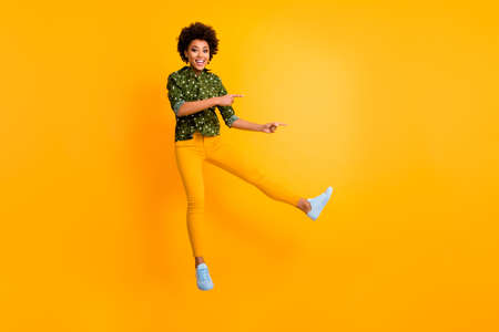 Full length photo of funny dark skin curly lady jumping high indicating fingers empty space low prices banner wear green dotted shirt pants isolated yellow color background