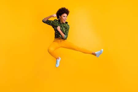 Full length photo of crazy dark skin curly lady jumping high making fighting moves ready to kick leg and fist wear green dotted shirt trousers isolated yellow color background