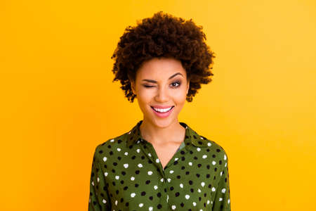 Photo of beautiful pretty dark skin wavy lady toothy beaming smiling winking eye flirty girlish mood wear green dotted shirt blouse isolated yellow color background