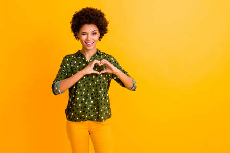 14-february its cool. Cheerful funky afro american girl date make heart with hands show her romantic love symbol wink blink enjoy wear green pants outfit isolated shine color background Banco de Imagens
