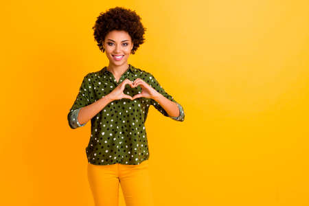 Portrait of positive cheerful afro american girl show her love symbol make heart with fingers enjoy 14-february affectionate holidays wear stylish outfit isolated bright color background