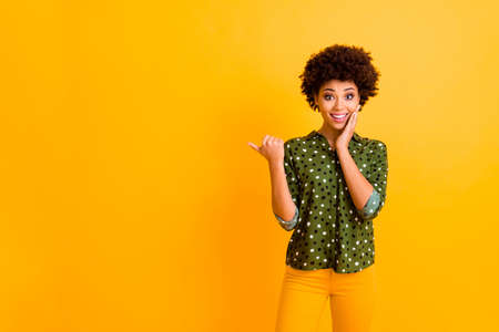 Photo of amazed dark skin curly lady indicate thumb finger empty space advising customers amazing low prices wear trendy green dotted shirt pants isolated yellow color background Reklamní fotografie - 135500242