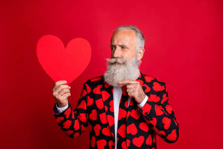 Close-up portrait of his he nice attractive amorous pensive creative gray-haired guy cherub holding in hand demonstrating paper heart isolated on bright vivid shine vibrant red color background