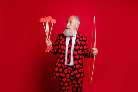 Portrait of his he nice attractive serious trendy white-haired guy wearing heart pattern cherub holding in hands arrows wedding isolated on bright vivid shine vibrant red color background
