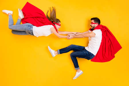 Top view above high angle flat lay flatlay lie view concept of his he her she funny cheerful cheery superheros flying having fun isolated on bright vivid shine vibrant yellow color background