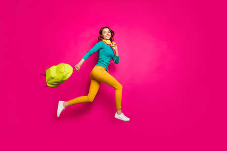 Full length body size side profile photo of cheerful positive nice pretty cute youngster wearing yellow pants trousers smiling toothily isolated pink vibrant color background Stock Photo
