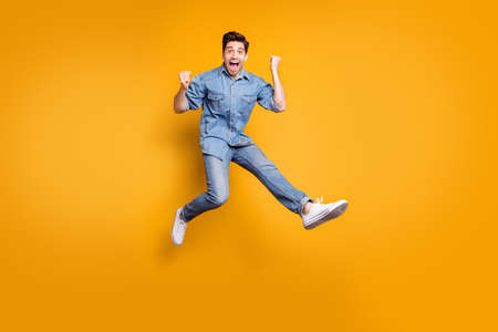 Full length body size photo of cheerful positive overjoyed man excited about having won competitions jumping up isolated vivid color background