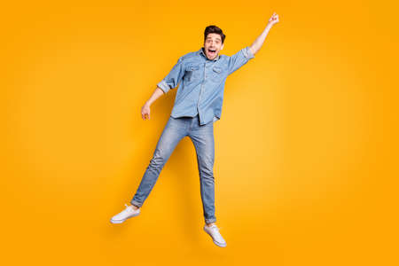 Full length body size photo of cheerful screaming positive man in white footwear flying away with umbrella by wind blowing isolated vivid color background