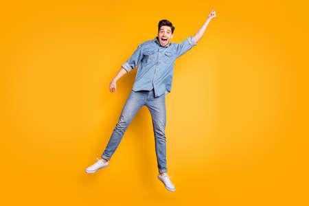 Ganzkörperfoto eines fröhlichen, schreienden, positiven Mannes in weißen Schuhen, der mit Regenschirm durch Wind weht, isoliert, lebendiger Farbhintergrund Standard-Bild