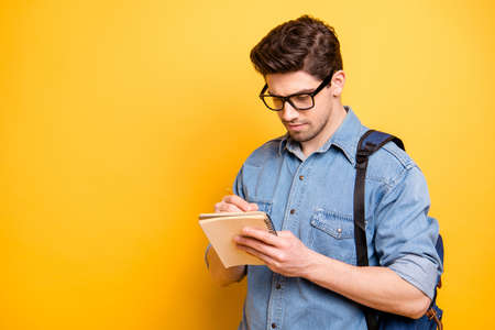 Photo of focused interested man planning organizing his future with satchel behind his back isolated writing new verse over vivid color background