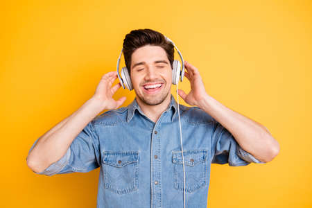 Close-up portrait of his he nice attractive cheerful cheery dreamy guy listening favorite music melody rhythm isolated over bright vivid shine vibrant yellow color background Stock fotó