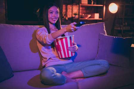 Foto von hübscher Dame inländischer Stimmung mit TV-Fernbedienung, die die Kanäle wechselt und Popcorn-Filmabend isst, bequeme Couch, lässiges Outfit, dunkles Wohnzimmer drinnen sitzend Standard-Bild