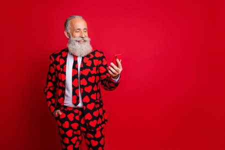 Photo of funny mature guy holding telephone chatting girlfriend write love sms letter wear stylish hearts pattern suit blazer shirt tie pants isolated red color background Imagens