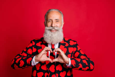 Close-up portrait of his he nice attractive cheerful cheery glad amorous friendly bearded white-haired man showing heart gesture isolated over bright vivid shine vibrant red color background