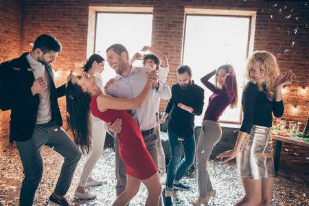 Foto di una bella coppia allegra e positiva di una coppia amata che si diverte insieme circondata da persone che ballano alla festa di compleanno Archivio Fotografico