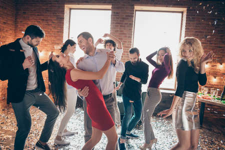 Photo of cheerful positive nice pretty couple of laughing beloved couple having fun together surrounded by people dancing at birthday party Stock Photo