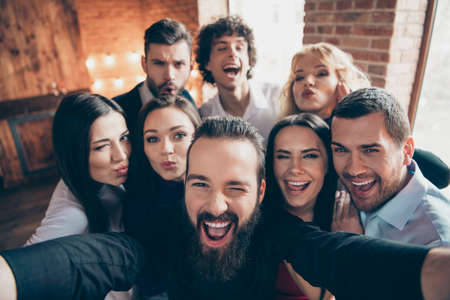 Photo of cheerful nice cool company of people fooling in front of camera near friend taking selfie kissing winking in formalwear Stock fotó