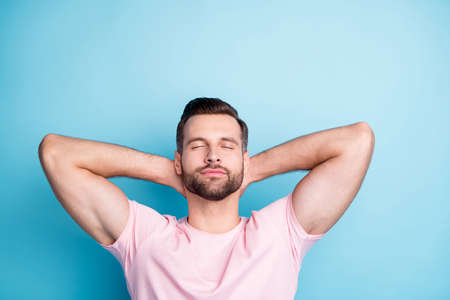 Photo of attractive guy holding hands behind head eyes closed enjoy amazing weekend day relaxing wear casual pink t-shirt isolated blue color background