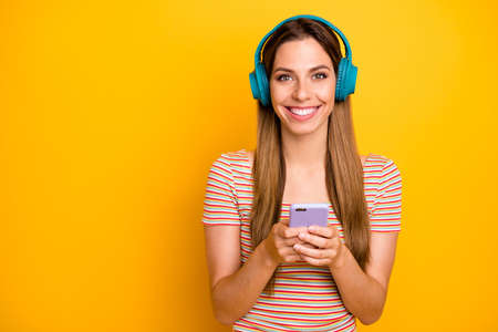 Photo of beautiful lady holding telephone listen music in cool wireless earphones choosing next song wear casual striped t-shirt isolated yellow color background