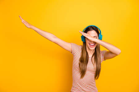 Photo of beautiful lady good mood listen music in cool wireless earphones dancing strange youth moves wear casual striped t-shirt isolated yellow color background