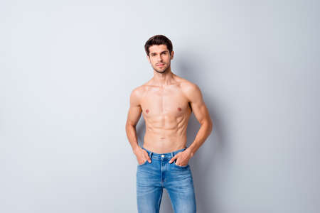 Portrait of his he nice attractive content cool fashionable muscular shirtless guy perfect figure form shape wearing jeans isolated over light white gray color pastel background Banque d'images