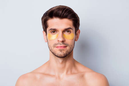 Close-up portrait of his he nice attractive well-groomed bearded brown-haired guy wearing eye facial patches modern uplift rejuvenation effect isolated on light white gray color pastel background Stock Photo