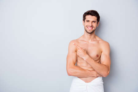Portrait of handsome brown hair guy enjoy spa salon man skin body care treatment point index finger copyspace wear white towel isolated over grey color background