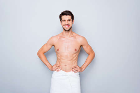 Portrait of positive guy having spa skincare procedure enjoy smooth flawless effect stand in bathroom with white towel isolated over grey color background Banque d'images