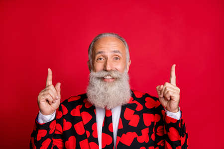 Close-up portrait of his he nice attractive cheerful cheery glad confident gray-haired man pointing two forefingers up ad advert isolated on bright vivid shine vibrant red color background