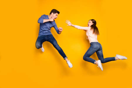 Full body photo of two ninja woman man have fight battle jump kick legs hands feel crazy wear pink blue sweater denim jeans sneakers isolated over yellow color background Stock Photo