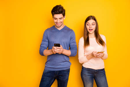 Suspicious woman want know what her husband post in his blog use cell phone look smartphone screen wear pink blue pullover denim jeans isolated over shine color background