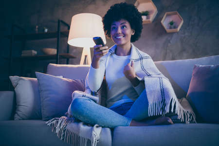 Cheerful afro american girl having free time watch tv film hold remote control switch channels sit divan crossed legs cover checkered blanket in evening room house indoors
