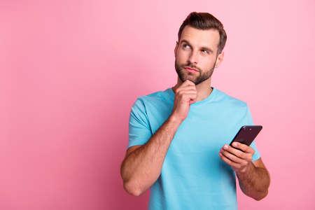 Photo d'un homme rusé et rusé intéressé touchant son menton regardant dans un espace vide à la recherche de nouveaux choix fond de couleur pastel isolé