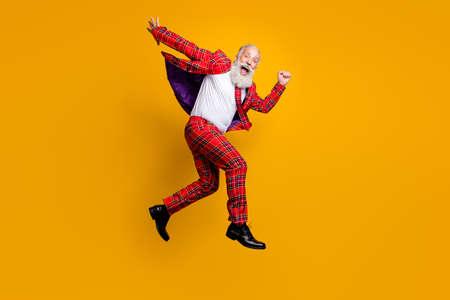 Ganzkörperansicht seines hübschen, fröhlichen, fröhlichen, funky Comics, verspielt, überglücklich, grauhaariger Mann, der isoliert über hell leuchtendem, leuchtend gelbem Farbhintergrund springt Standard-Bild