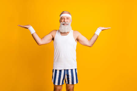Photo of aged senior model white hair guy presenting new sports products advising two best wear tank-top striped shorts sweatband isolated yellow color background