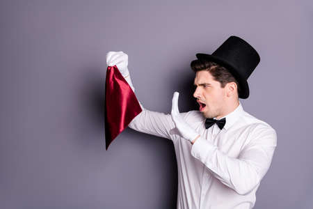 Profile side photo of funky wizard conjurer hold red napkin say spells want show focus wear white stylish shirt bow tie hat isolated over grey color background