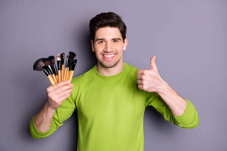 Photo of handsome worker guy hold new visage master brushes raising thumb up advising good quality express agreement wear green casual sweater isolated grey color background