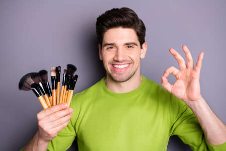 Close up photo of confident cool visagist worker man hold tassels brushes show okay sign suggest great party evening make-up wear green pullover isolated over grey color background