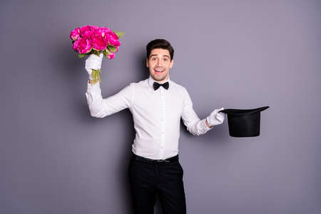 Flowers for madam. Photo of handsome show man hold black wizard cylinder getting fresh peonies bunch from inside wear white shirt bow tie trousers isolated grey color background