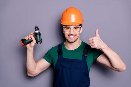 Portrait of handsome man repairer successful handyman hold perforator show thumb up sign wear orange hard hat green t-shirt protective goggles isolated over grey color background