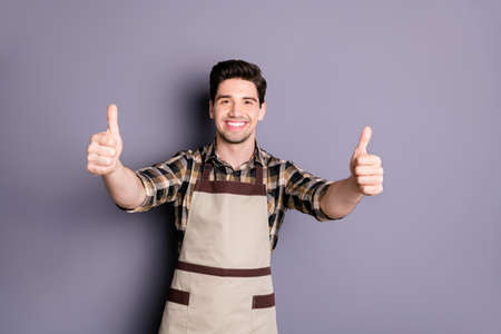Photo of cheerful fun positive handsome man smilt toothy showing thumbs up to emphasize quality isolated grey color background