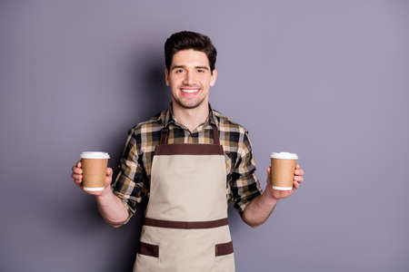 Photo of attractive worker guy holding hands two paper coffee cups inviting visitors try aroma coffee professional barista wear apron plaid shirt isolated grey color background
