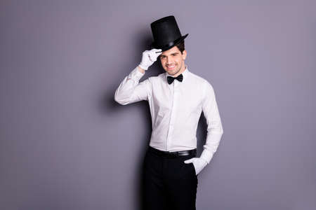 Portrait of cool attractive wizard man ready perform circus stage touch cylinder black hat wear white classic shirt bow pants gloves isolated over grey color background