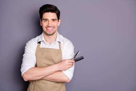 Profile photo of attractive worker guy hold hairdo cutting tools scissors comb hair stylist professional inviting customer sit down wear apron white shirt isolated grey color background