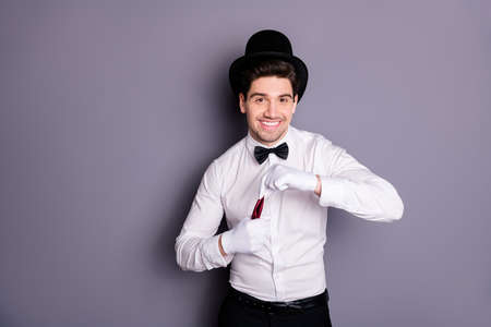Portrait of positive cheerful wizard man hide red napkin in white gloves make focus spells wear white shirt black bow cylinder hat isolated over grey color background