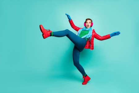 Foto de perfil de cuerpo completo de dama asustada levantar la pierna alta caminar camino resbaladizo caer hacia abajo usar abrigo rojo casual bufanda orejeras rosa pantalones guantes de puente zapatos aislado fondo de color verde azulado Foto de archivo